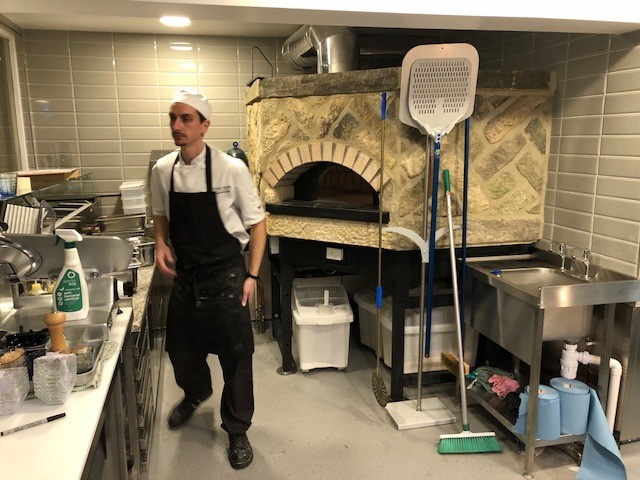 Man operating Pizza oven in Boun Apps